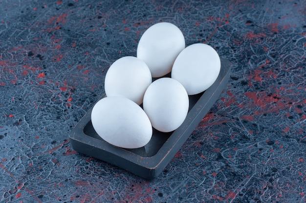 Una tavola di legno scuro con uova di gallina bianche crude.