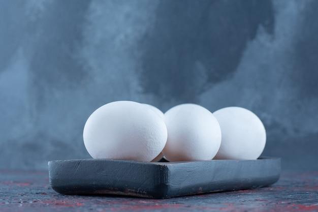 Una tavola di legno scuro con uova di gallina bianche crude