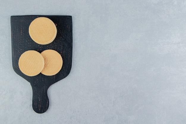 Una tavola di legno scuro con dolci biscotti rotondi.