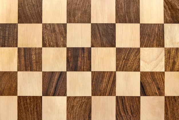 暗い木製のチェス盤の市松模様の背景
