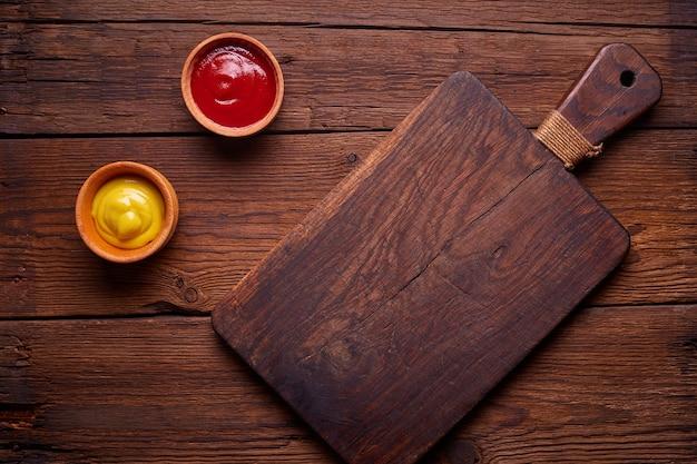 暗い木製のまな板と暗いキッチンテーブル、上面にソース