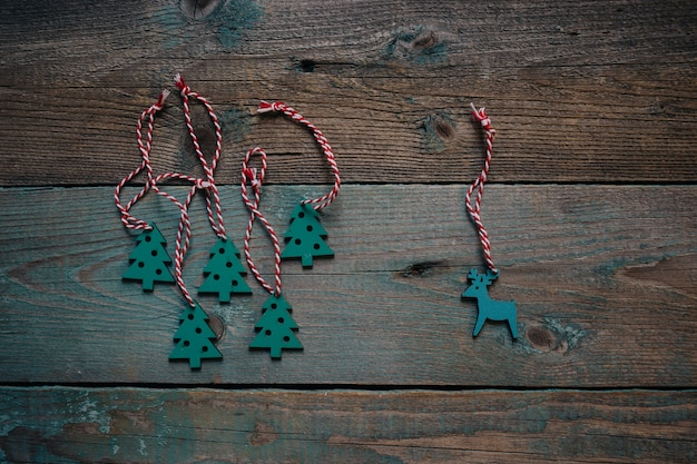 Dark wooden flat lay with wooden decoration deer and christmas trees. winter holiday compo
