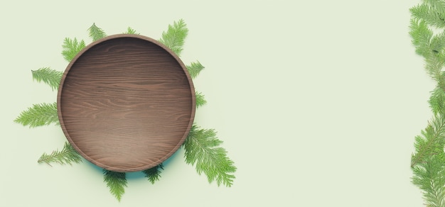 Dark wooden plate with pine leaves underneath and on the side on pastel green surface