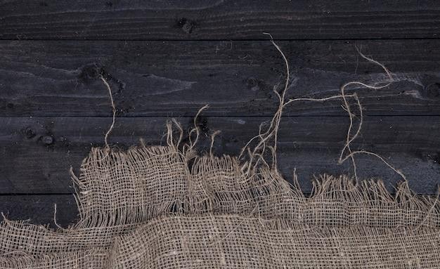 黄麻布、トップビューで暗い木製のテーブル背景