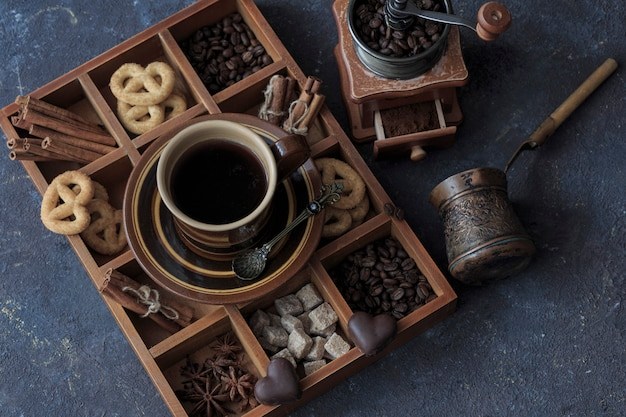 On a dark wooden table a cup of coffee, chocolate and pretzels in a box, a coffee grinder