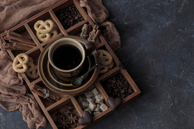 On a dark wooden table a cup of coffee, chocolate and pretzels in a box