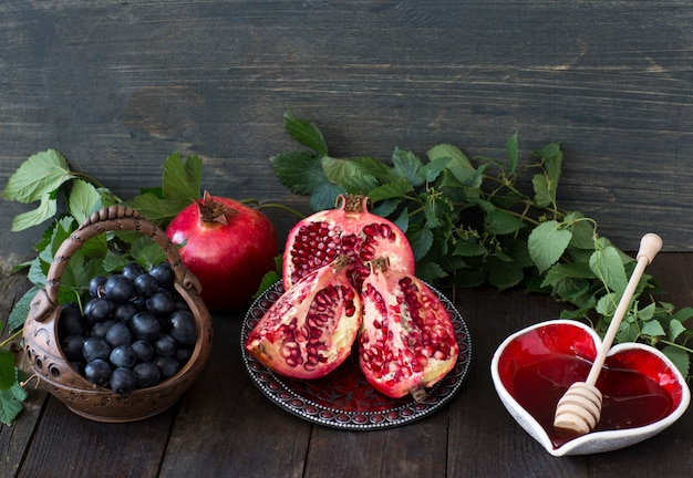 On a dark wooden table, grapes in a basket, honey and pomegranate