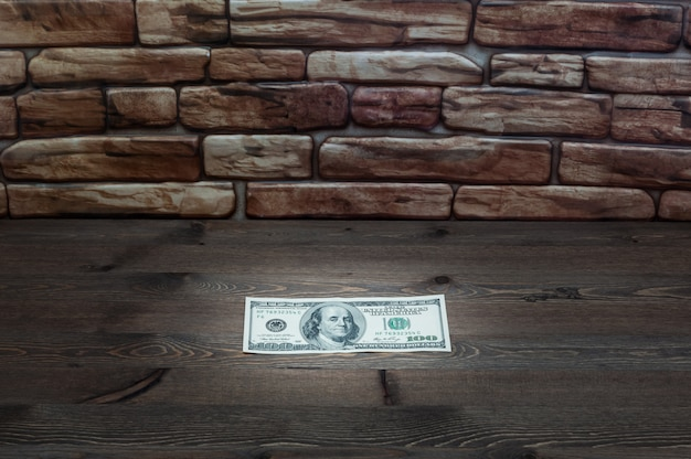 On a dark wooden table near a brick wall of a bill one hundred dollars lit by a ray of light.