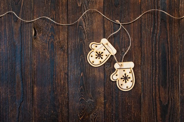 Dark wooden texture and christmas toys in the form of mittens and copyspace background