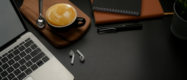 Dark worktable with laptop, schedule books, coffee cup, wireless earphone and copy space