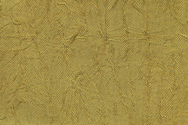 Dark yellow wavy a textile material. fabric with fold texture closeup.