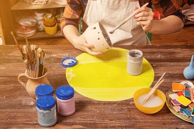 Темноволосая гончарша в клетчатой рубашке улыбается и рисует глиняным подсвечником с кисточкой.