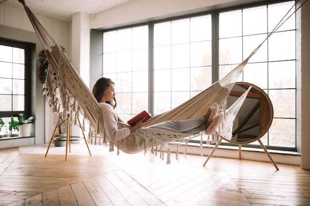 ズボンのセーターと暖かいスリッパに身を包んだ黒髪の少女は、居心地の良い部屋のハンモックに横たわっている本を読みます