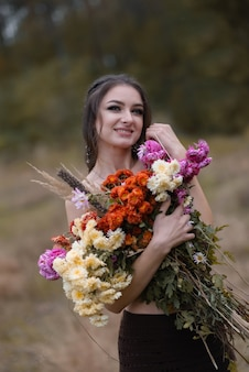 Darkhaired girl holding a large bouquet of flowers and looking at the camera