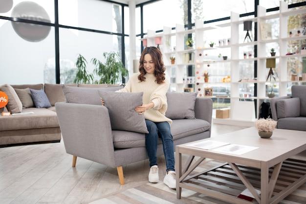 灰色のソファに座っている白いシャツとジーンズの黒髪の女性