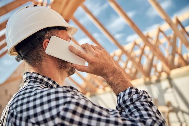 전화를 걸고 보호 헬멧에 검은 머리 젊은 건축업자