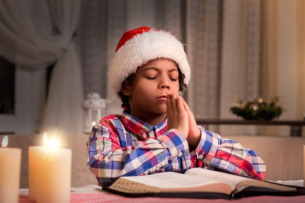 Darkskinned boy praying on christmas little santa prays to god purity of young soul prayer after rea...