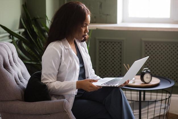 Темнокожая женщина-врач разговаривает по скайпу с ноутбуком