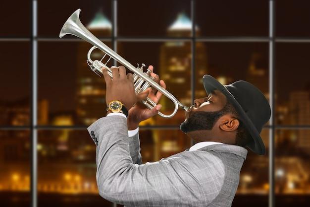 Темнокожий трубач в шляпе-федоре.