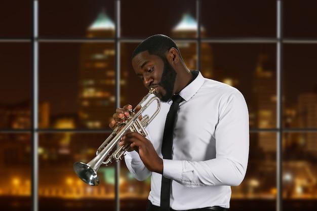 Темнокожий трубач в белой рубашке.