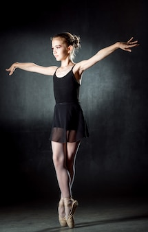 バレリーナ。ポーズとスタジオで踊るかわいい女の子。リトルダンサー。 darkwallblackドレス。