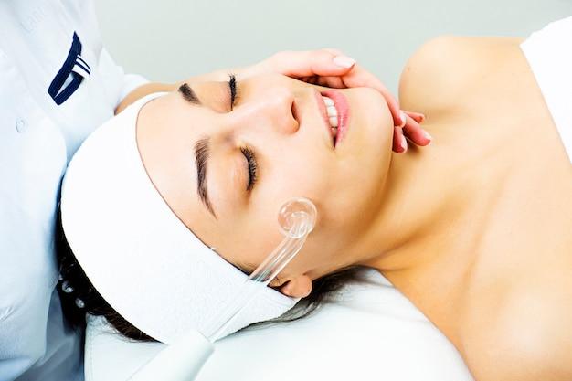 顔のdarsonvalization。手順女性の顔のクローズアップのdarsonvalization。