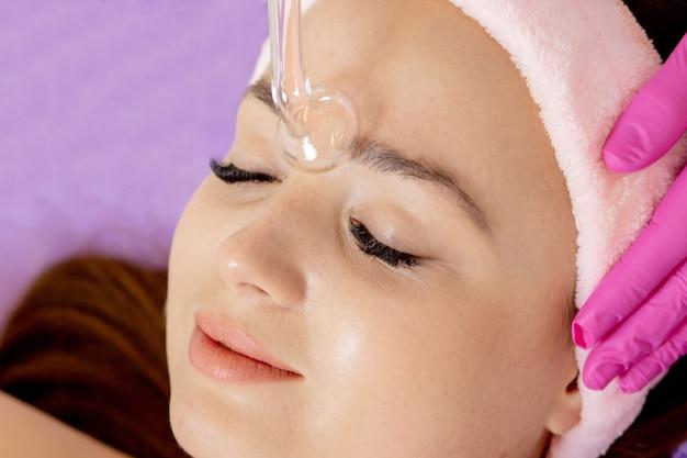 전기 요법의 도움으로 얼굴의 darsonvalization 또는 얼굴의 회춘. 얼굴에 대한 darsonval의 사진. 현재 치료법. 환자는 미용실에 있습니다.