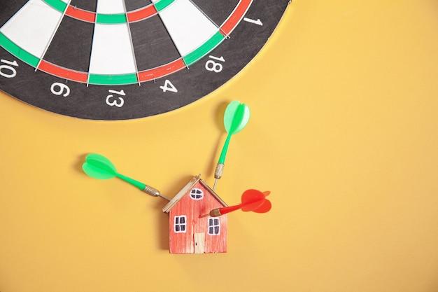 Стрелка дротика, мишень и модель дома на желтом фоне.