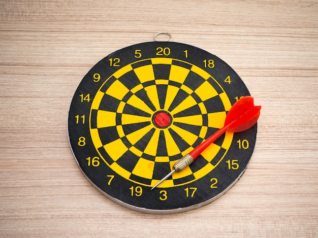 Dart arrow and dartboard on brown wooden background