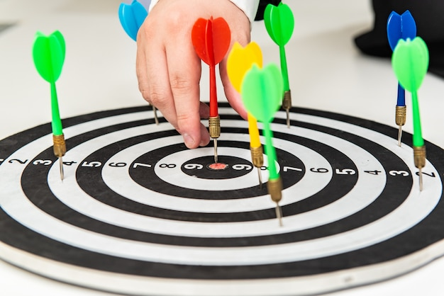 Dart arrow in hand on target dartboard, goal and target setting in business concept.