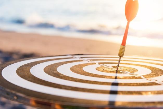 Dart arrow hit center on bullseye of a dartboard is a target of challenge business