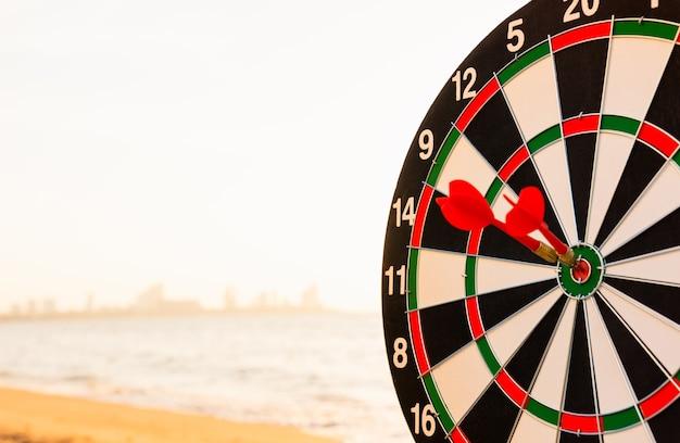 Dart arrow hit to center on bullseye dartboard is target of purpose challenge business at sunset