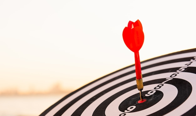 Dart arrow hit to center on bullseye dartboard is a target of purpose challenge business at sunset