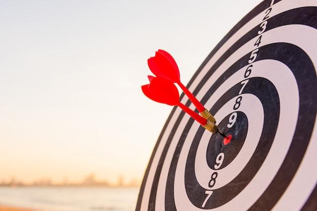 Dart arrow hitting to center on bullseye dartboard is the target of purpose challenge business