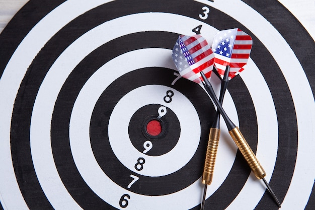 Dart arrow hitting in the target center of dartboard.