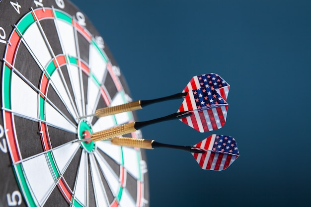 Dart arrow hitting in the target center of dartboard.