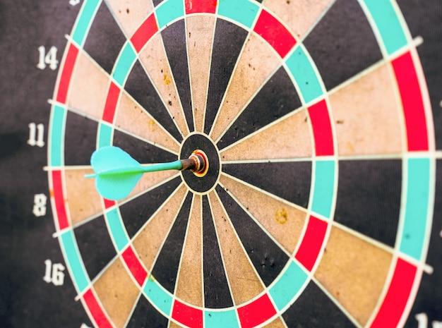Dart in bullseye center of target on aged dartboard