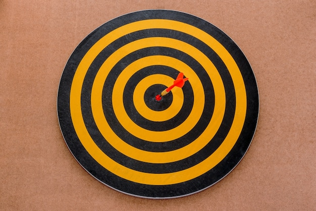 Dart hitting a target on brown background