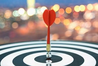 Dart target arrow on bullseye over blurred bokeh background