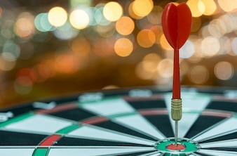 Dart target arrow on bullseye over bokeh background