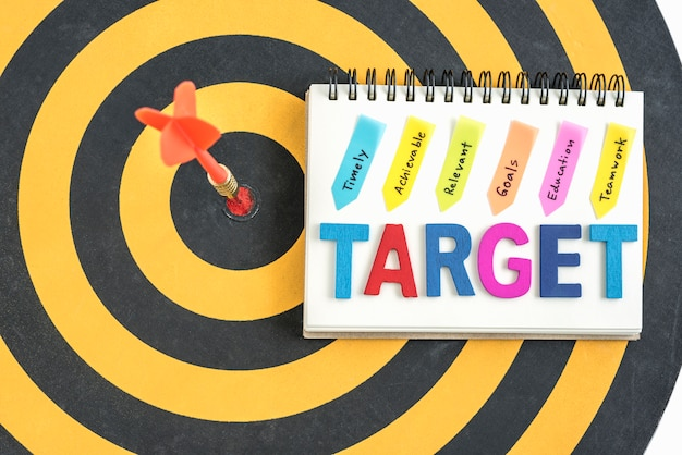 Dart target in bullseye with words target on the notebook with handwriting timely achievable relevant goals education teamwork over dartboard background, business success concept