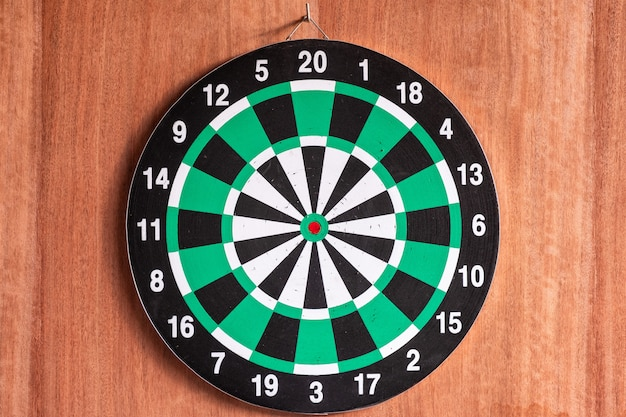 Dartboard hanging on wooden wall