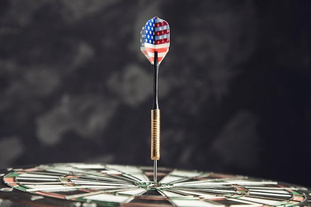 어두운 벽에 미국 국기와 다트 화살표