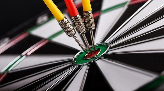 다트 판이 중앙에 빨간색과 노란색 다트 화살표가있는 다트 보드. 타겟팅, 비즈니스 및 성공 개념.
