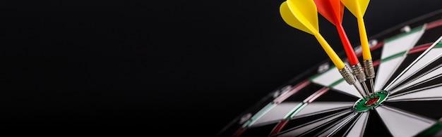 다트 판 중앙에 빨간색과 노란색 다트 화살표가있는 다트 보드. 타겟팅, 비즈니스 및 성공 개념.