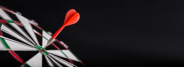 Darts board with red dart arrow on center of dartboard