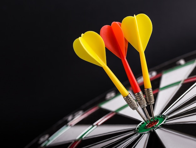 Darts board with red and yellow darts arrows on center of dartboard