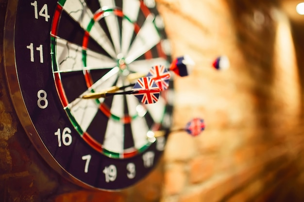 Darts hanging on a brick wall. darts with the english flag.