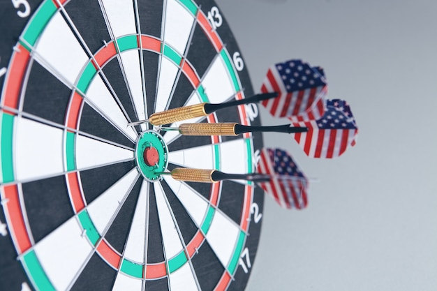 Darts with american flag hitting in the target center of dartboard