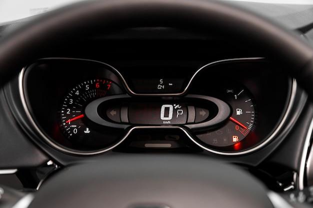 자동차의 대시보드는 밝은 조명으로 비춰집니다. 속도계, 원형 타코미터, 오일 및 연료량